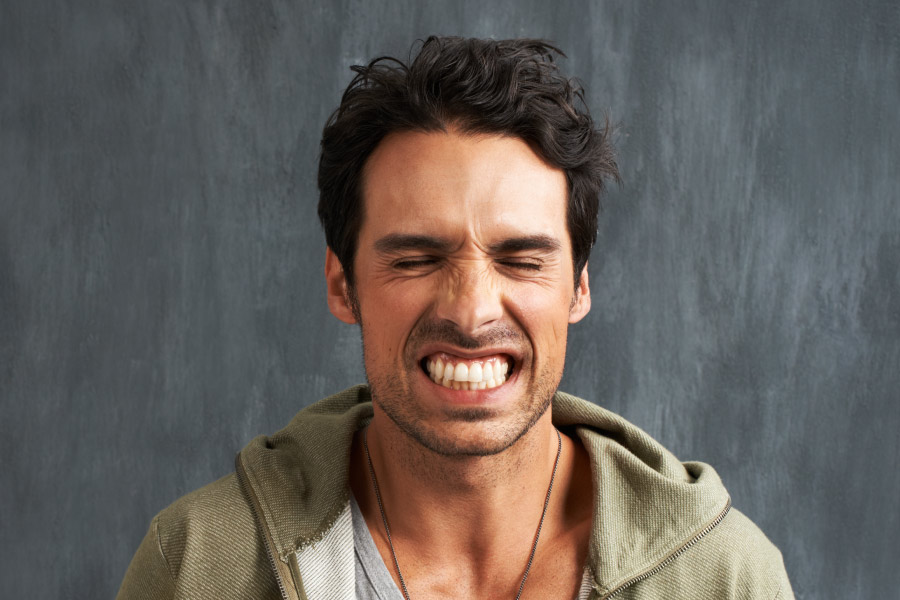 Brunette man grinds his teeth because of stress that is negatively affecting his quality of life and oral health