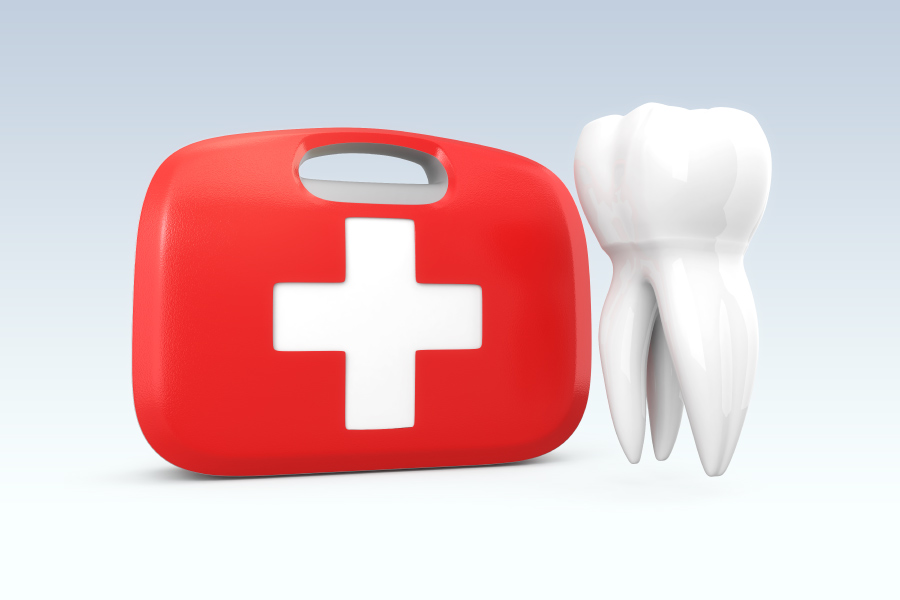 A first aid kit next to a tooth for a blog post about dental emergencies