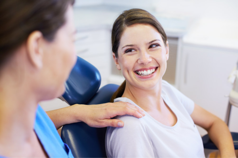 Brunette woman smiles at the dentist in Wilmington, NC